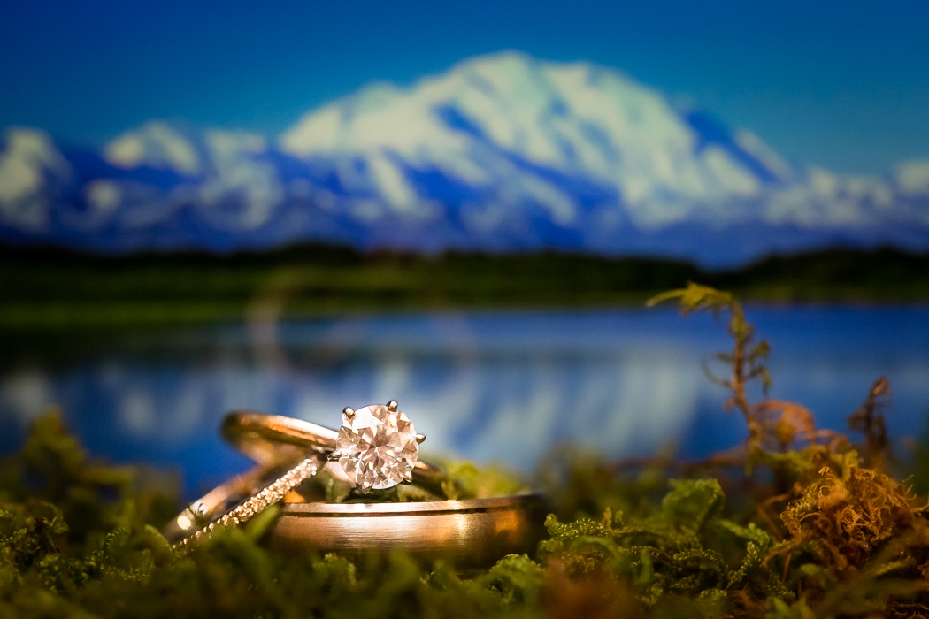 wedding rings sit in moss with Wonder Lake , Denali National Park AL in background