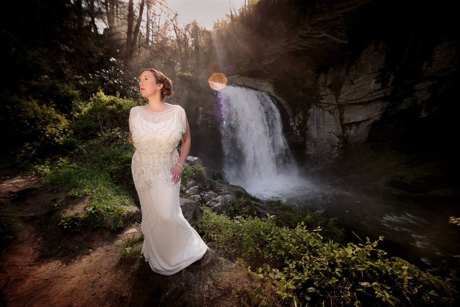 Bride in wedding dressing standing near Pisgah National Forest waterfall during bridal session