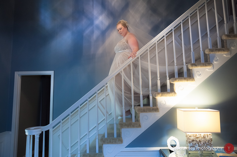 bride walking down staircase with hand on railing and train falling behind
