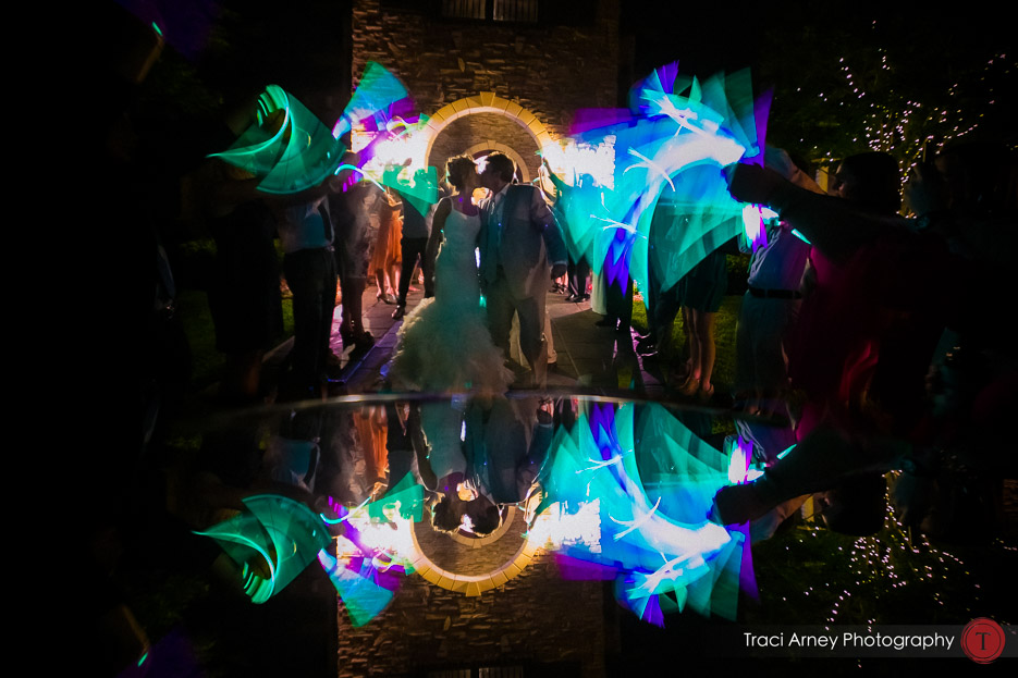bride and groom exiting wedding with glowsticks and reflected in mirror at vineyard wedding