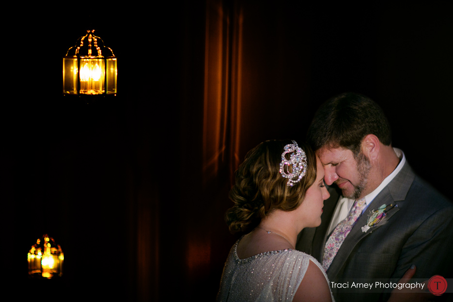 bride and groom in softly lit but graphic dark stairwell
