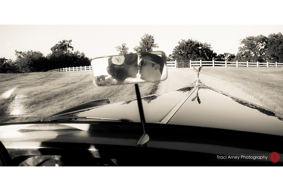 bride and groom seen kissing in rear view mirror of their rolls royce get away car at an outdoor wedding at Adaumont Farms at Trinity, NC