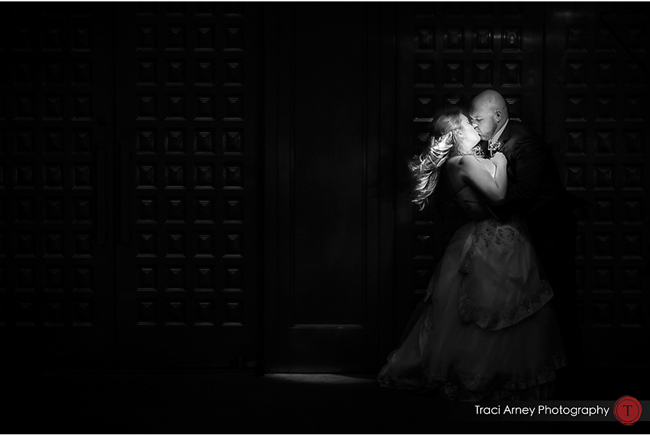 Graphic black and white image of bride and groom in spotlight